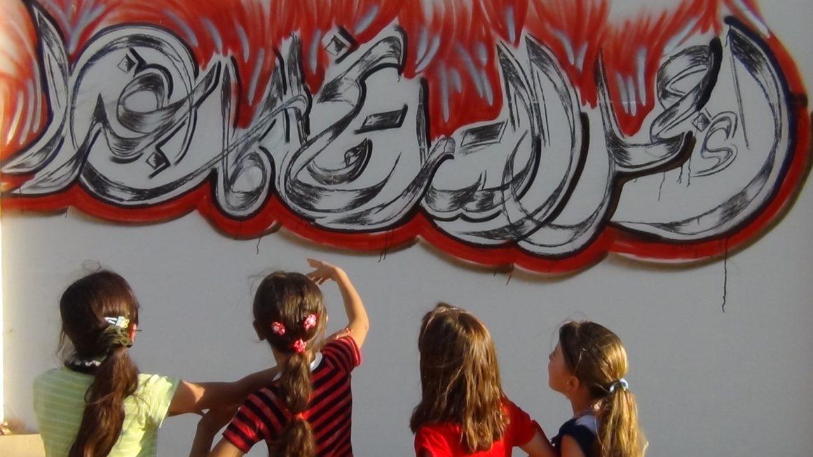 Syrië2012-Meisjes-kijken-naar-slogan-in-Saraqeb-c-Eyad-al-Jaroud-RF.jpg